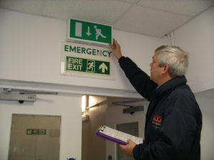 Electrical Testing Surveyor checking emergency exit lights