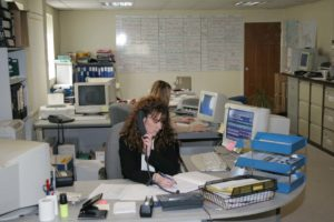 Electrical Testing Surveyors ltd customer service representatives sitting at desks with telephones and computer screens.