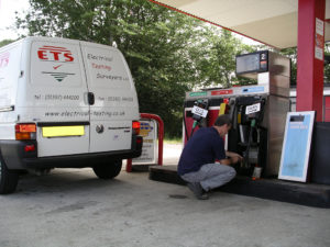 Electrical testing surveyor testing the electrics of a petrol pump
