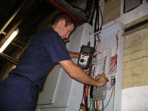 Electrical testing surveyor checking safety of an electrical Distribution Board