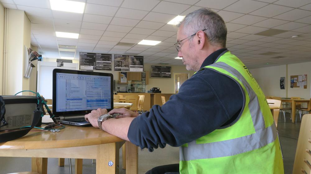 Electrical Testing Surveyor using electrical testing software on a laptop